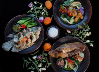 Many various dishes top view. Fish, duck, chiken on dark background