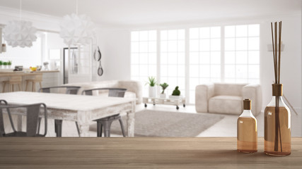 Wooden table top or shelf with aromatic sticks bottles over blurred scandinavian living room with dining table and sofa, white architecture interior design