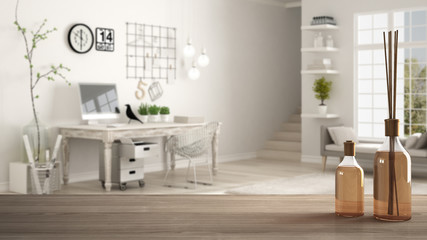 Wooden table top or shelf with aromatic sticks bottles over blurred scandinavian home workplace, white architecture interior design