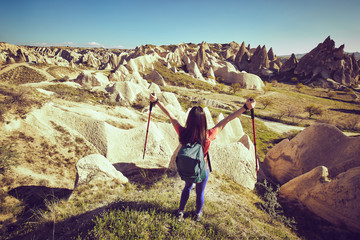 Traveler woman raised hands discovering mountains  with backpack.