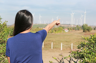 Rear view of woman pointing of wind turbine field.