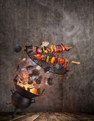 Kettle grill with hot briquettes, cast iron grate and tasty skewers flying in the air. High resolution image.