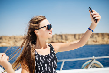 Young beautiful brunette girl making selfie using phone while relaxing on the luxury yacht