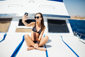 Young beautiful girl making selfie using phone while sitting on the luxury yacht