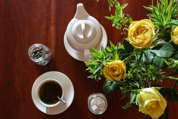 Above view of a tea cup and tea pot with yellow roses