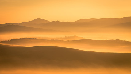 Tuinposter Ochtendgloren Picturesque sunrise in Tuscany, Italy. Misty morning with light fog shapes magically the hills and valleys of this beautiful tourist location in San Quirico d'Orcia region. Horizontal image