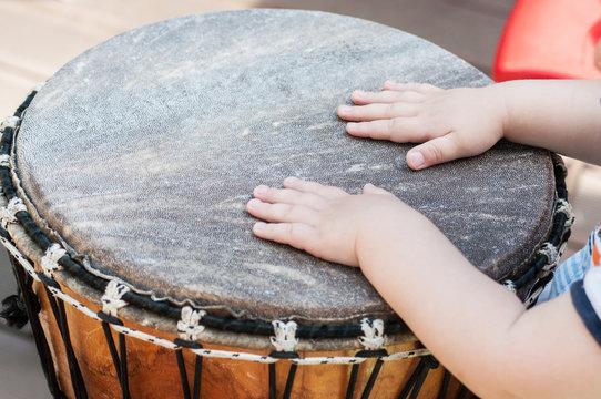 closeup of baby hands on african drums in outdoor