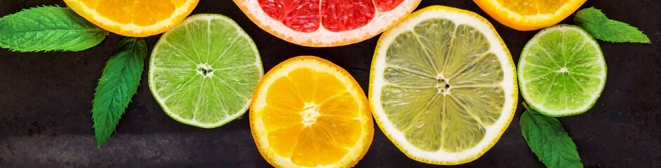 Banner of corner with slice of oranges, lemons, limes, grapefruit and mint pattern on black. Flat lay