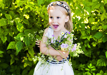 The little, happy girl with flowers in a summer garden