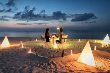 Paar sitzt beim privaten, romantischen Abendessen am tropischen Strand bei Sonnenuntergang