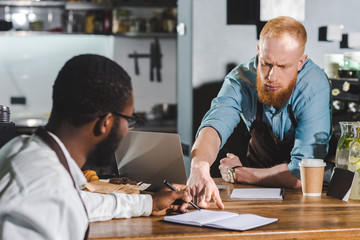 young serious male barista pointing by finger on textbook to colleague