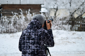 Young, unknown photographer taking outdoor pictures with  telephoto lens at winter time.