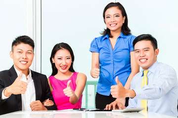 Cheerful Asian Chinese financial consultants in office