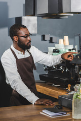 handsome young african american barista in eyeglasses pointing at screen while working in cafe