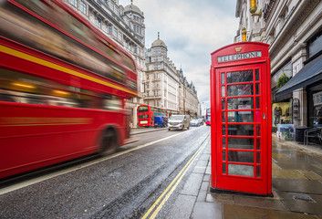 Photo sur Plexiglas Londres London, England - Iconic blurred vintage red double-decker bus on the move with traditional red telephone box in the center of London at daytime