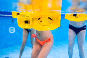 Group in water physical therapy training with resistance devices, underwater shot