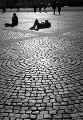Girls sitting on the pavement of the palace square with backlighting of the sunlight