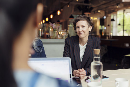 Woman sitting in restaurant, looking at camera