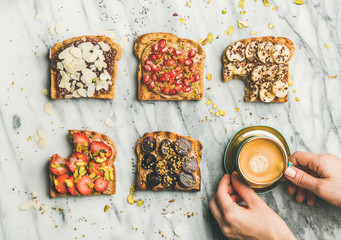 Healthy breakfast, snack. Flat-lay of vegan wholegrain toasts with fruit, seeds, nuts, peanut butter, cup of espresso and woman hands over light marble background, top view. Clean eating food concept