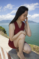 Close up of woman kneeling on cliff by ocean
