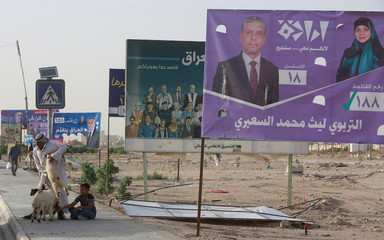 A man holds a sheep for sale next to campaign posters of candidates ahead of parliamentary election, in Najaf