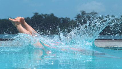 CLOSE UP: Unrecognizable girl dives into crystal clear pool on hot summer day. Wall mural