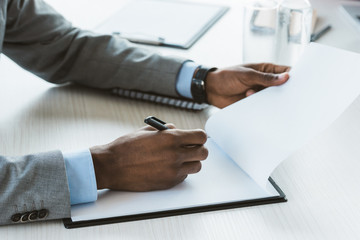cropped shot of african american businessman writing on blank clipboard