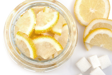 Pieces cut of lemon in a glass bowl and of sugar on a white background