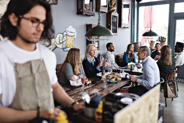Customers having brunch while young male owner standing in lectern