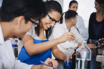 Smiling multi-ethnic students mixing solutions at chemistry laboratory