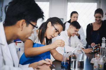 Young multi-ethnic students mixing solutions at chemistry laboratory