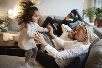 Girl playing with grandmother on sofa by family at home