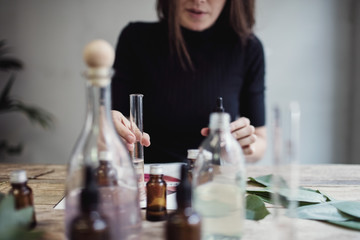 Midsection of female owner mixing liquid while sitting at table against wall in perfume workshop