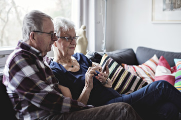 Senior couple using smartphone at home