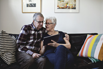 Senior couple sitting on sofa while sharing digital tablet against wall at home