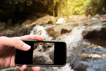 the tourist shooting waterfall with smartphone.