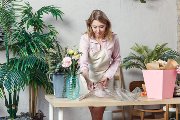 Photo of florist woman cutting film at table with flowers, paper