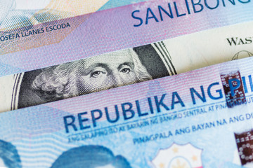 United States one-dollar bill, George Washington peeking through Philippines one thousand peso bills.