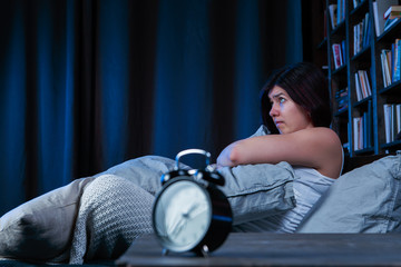 Picture of dissatisfied brunette with insomnia sitting on bed next to alarm clock