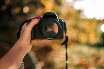 woman's hand taking a reflex camera