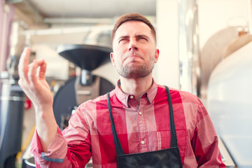 Image of happy barista in apron on background of industrial coffee grinder