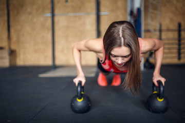 Photo of spotswoman doing horizontal push-ups with kettlebells