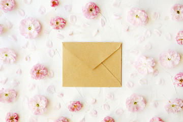 Blank closed craft paper envelope for mother's day with copy space for text among pink flowering blossoms on white background. Minimal composition with flowers and piece of paper. Close up, top view.