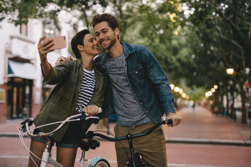 Romantic couple taking selfie with bicycles