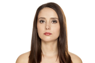 Portrait of young serious woman with makeup on white background