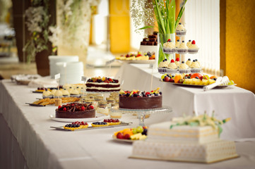 Many various cakes and desserts in candy bar at venue wedding celebration reception