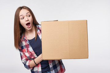 Delivery, relocation and unpacking. Excited young woman holding cardboard box, looking at blank copy space at box, surprised, isolated