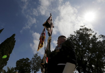 Flag bearers stand at attention during a service to mark the 100th anniversary of ANZAC landings at Gallipoli, at the Pieta Military Cemetery in Pieta, Malta