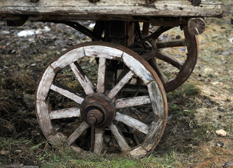 Fragment of the old horse cart with a wooden wheel