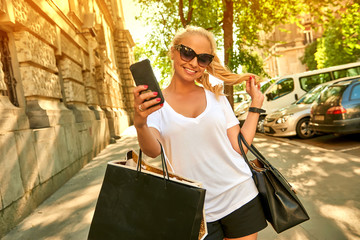 Young woman taking selfies on the street with bags